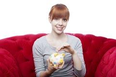 Young girl put coin in piggybank Royalty Free Stock Photos
