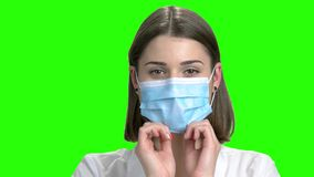 Young girl put on protective medical mask. Close up face. Green screen hromakey background for keying stock video footage