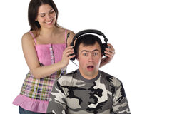 The young girl puts on the guy headphones Royalty Free Stock Image