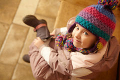 Young Girl Putting On Boots. Young Girl Sitting On Wooden Seat Putting On Warm Outdoor Clothes And Boots Royalty Free Stock Image