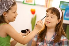 Young girl putting makeup on friend Royalty Free Stock Photos