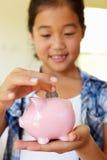 Young girl putting money in piggybank Royalty Free Stock Photos