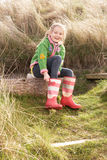 Young Girl Putting On Wellington Boots. In the sun Royalty Free Stock Photos