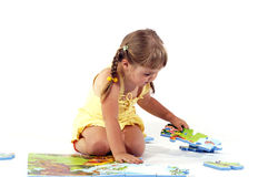 Young girl and puzzles. Isolated white background Royalty Free Stock Images