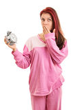 Young girl in pyjamas holding an alarm clock Royalty Free Stock Image