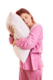 Young girl in pyjamas holding a pillow Stock Photos