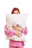 Young girl in pyjamas hugging a pillow Royalty Free Stock Photography