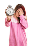 Young girl in pyjamas overslept. Oh my, there goes my timing of things. Young girl in pyjamas holding an alarm clock isolated on white background Stock Images