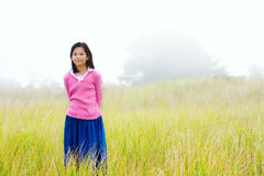 Young girl quietly standing on misty foggy field Royalty Free Stock Image