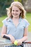 Young girl with racket on tennis court smiling Stock Image