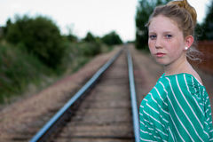 Young girl on rail tracks. A young adolescent girl looks on while on a set of railroad tracks Royalty Free Stock Photography