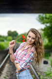 Young girl on the railroad with red poppy flowers Stock Images