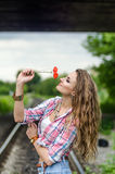 Young girl on the railroad with red poppy flowers Stock Photo