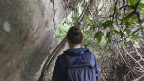 Young girl in raincoat going down the stair on wood trail during travel. Hiking woman with backpack walking in tropical stock video