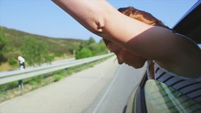 Young girl raise hands, scream out of open window of driving car. Wind. Smile. Traveling. Journey