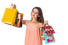Young girl raised in the hands of large coloured packages  stores isolated on white background Royalty Free Stock Photography