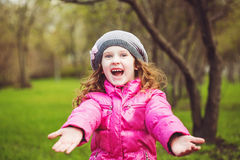 Young girl raised for hands to doing hug, says welсom. Stock Photos