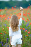 Young girl with raised hands to the top. View from the back Stock Images