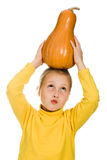 The young girl raised her pumpkin over his head Stock Image