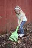 Young Girl Raking Outside with Toy Rake Royalty Free Stock Photos