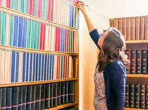 Girl Reaching for a Book on Bookshelf Royalty Free Stock Image