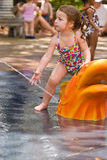 Young girl playing in water. A young girl reaching for a spray of water while watching other children at play Stock Images