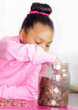 Reaching for the money. Young girl reaching in to her savings bank Stock Photography