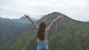 Young girl reaching up top of mountain and raised hands. Woman tourist standing on the edge of beautiful canyon stock footage