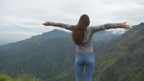 Young girl reaching up top of mountain and raised hands. Woman tourist standing on the edge of beautiful canyon stock video footage
