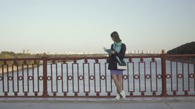 Young girl read the book at the bridge on river background stock video