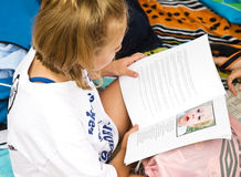 Young Girl Reading. A young girl sitting on towels reading a book. This could be at the beach, pool or home royalty free stock photo