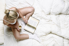 Young girl reading in bed Royalty Free Stock Photos