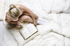 Young girl reading in bed Stock Photos