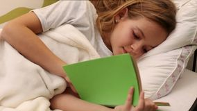 Young girl reading in bed. Closeup, sliding camera stock footage