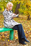 Young girl is reading on a bench Stock Image