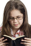 Young girl reading the Bible. Young girl with glasses reading the Bible royalty free stock images