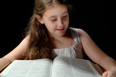 Young Girl Reading Bible. Young girl smiling while reading a large bible Royalty Free Stock Photo