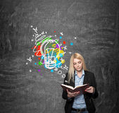 Young girl reading, blackboard with coloured image at the backgr Royalty Free Stock Photo