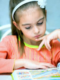 Young girl reading book. Portrait of young girl reading book indoors Royalty Free Stock Photography