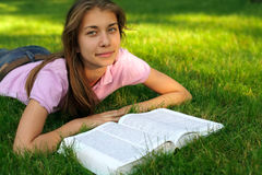 Young girl reading the book Stock Images