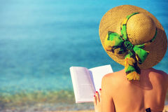 Young girl, reading a book at the beach Stock Photos