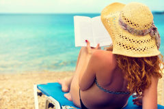Young girl, reading a book at the beach Stock Photo