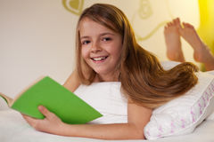 Young girl reading a book in bed Royalty Free Stock Photography