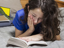 Young Girl Reading Book in Bedroom Royalty Free Stock Photos