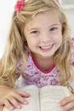 Young Girl Reading Book In Bedroom Stock Photography