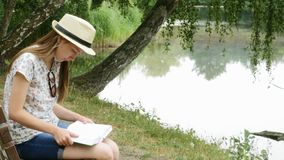 A young girl reading a book on a bench near the lake. A young girl in panama sits on a bench and reading a book in the city park on the lake stock footage