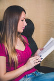 Young girl reading a book on the couch. In a cafe Royalty Free Stock Photography