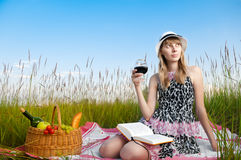 Young girl reading book and drinking wine Royalty Free Stock Photos