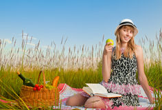 Young girl reading book and eating apple Royalty Free Stock Photography