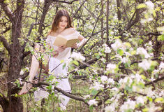 Young girl reading book in garden Royalty Free Stock Photo
